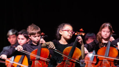 Children playing the cello on stage.