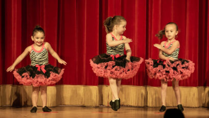 Young dancers on stage in red and black skirts.
