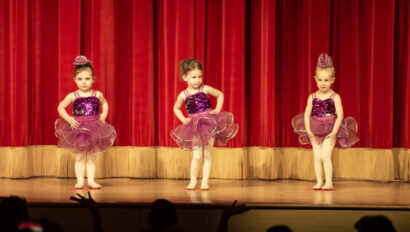 Young girls doing a ballet performance on stage.