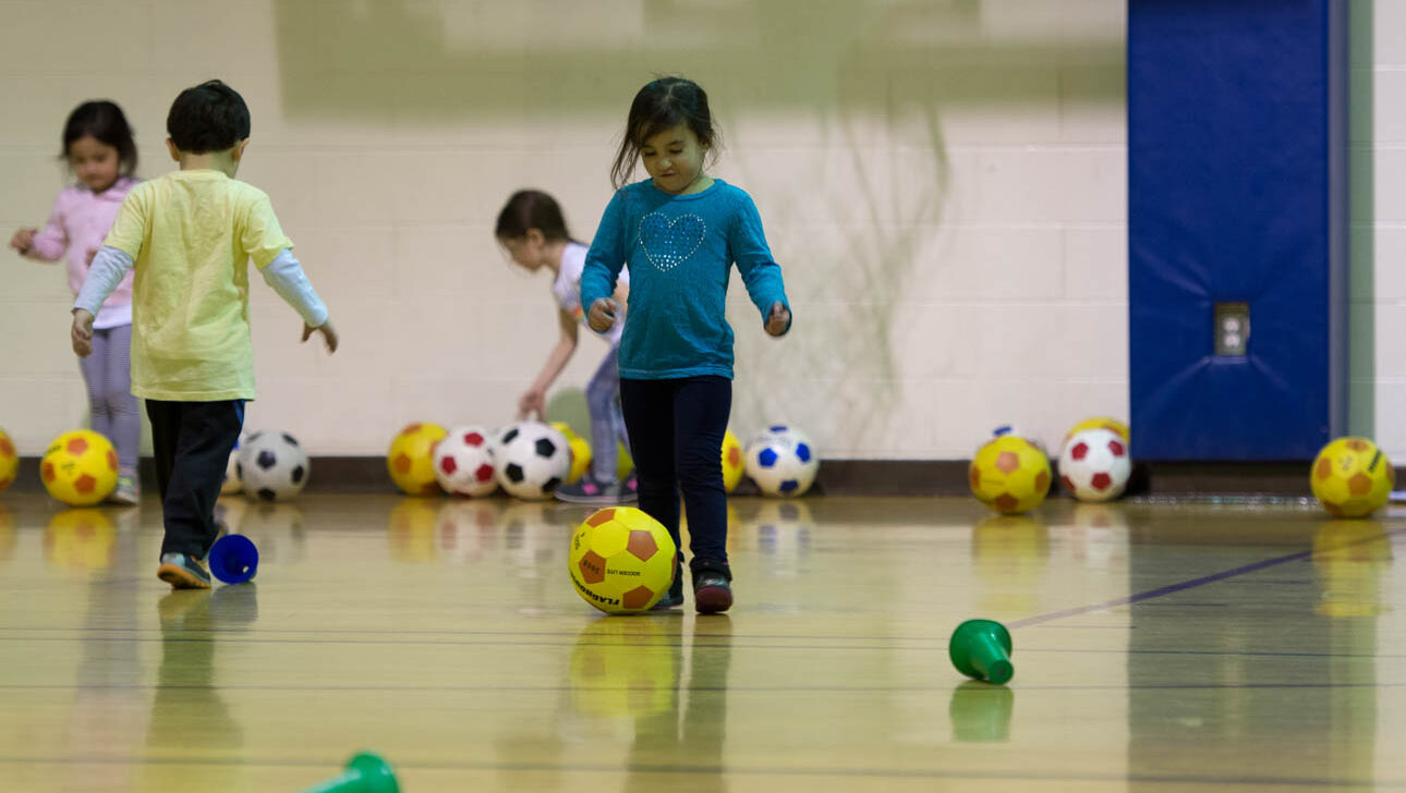 Girl playing soccer in a gym.