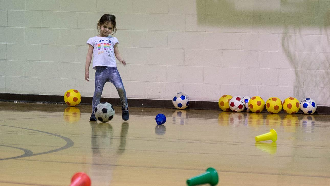 Girl playing soccer inside.