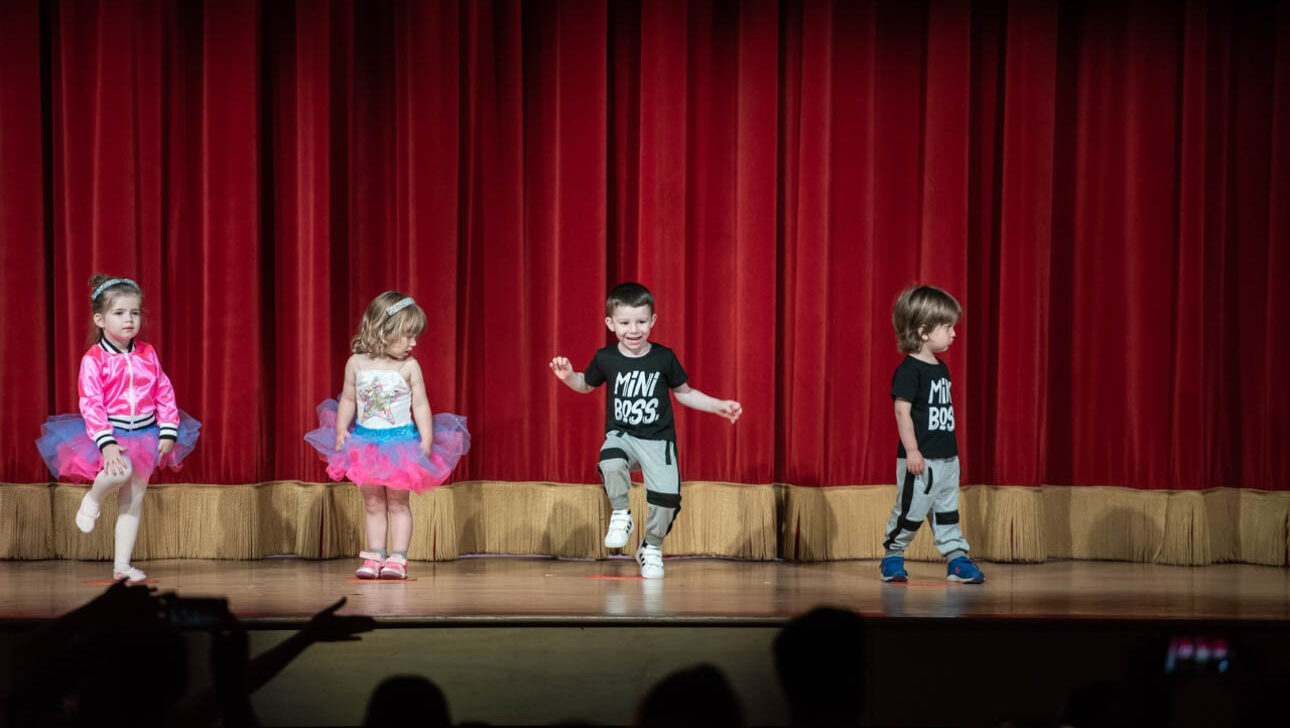 Toddlers doing a hip hop performance on stage.