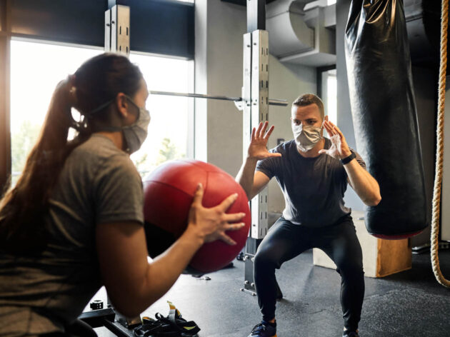 Woman throwing a medicine ball to a man in the gym.