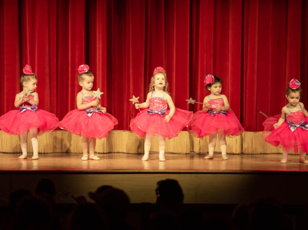 Five little girls in red tutus on stage.