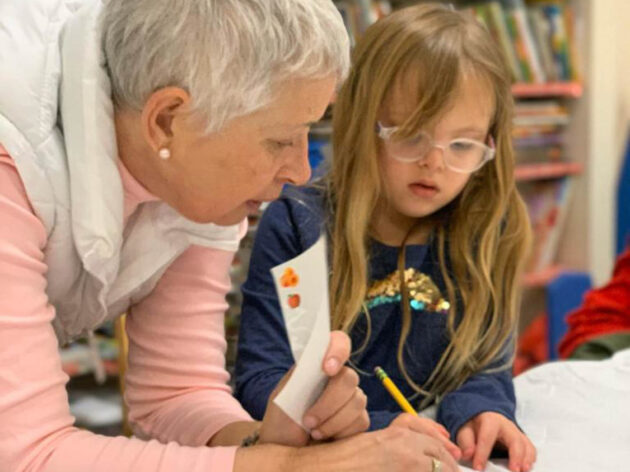 Teacher helping a young girl with her work.
