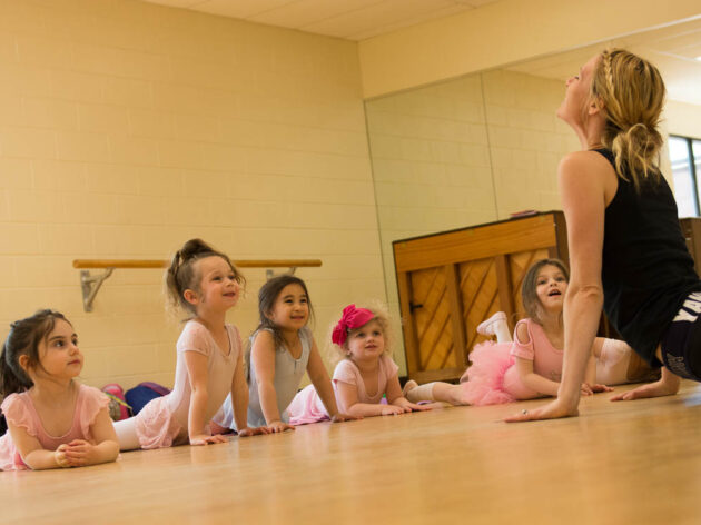 Early childhood dance students and teacher stretching in class.