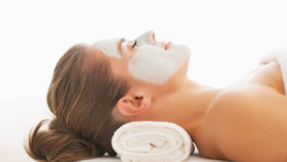Woman laying with a mud mask on her face.