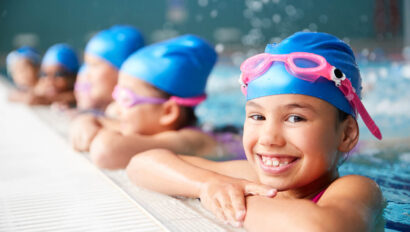 Kids in swim caps smiling at the pools edge.
