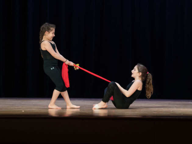 One girl pulling another girl up using a red piece of fabric on stage.
