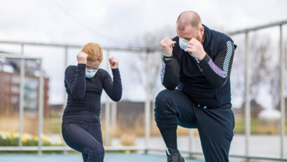 Woman and man boxing outside.