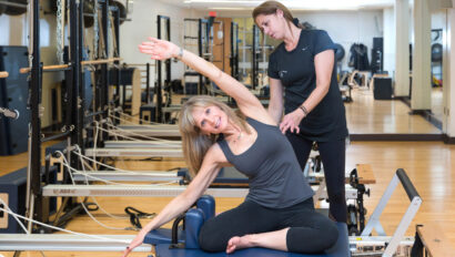 Woman assisting woman on the Pilates reformer machine.
