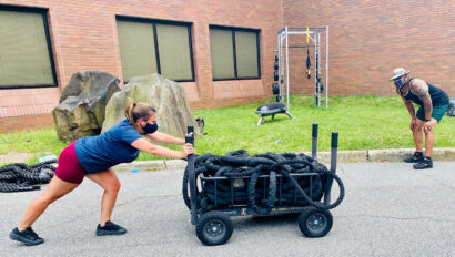 Woman pushing a cart pull of heavy ropes.