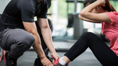 Trainer holding down feet of woman as she does a sit up.