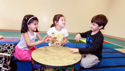 Three toddlers playing on a large drum.